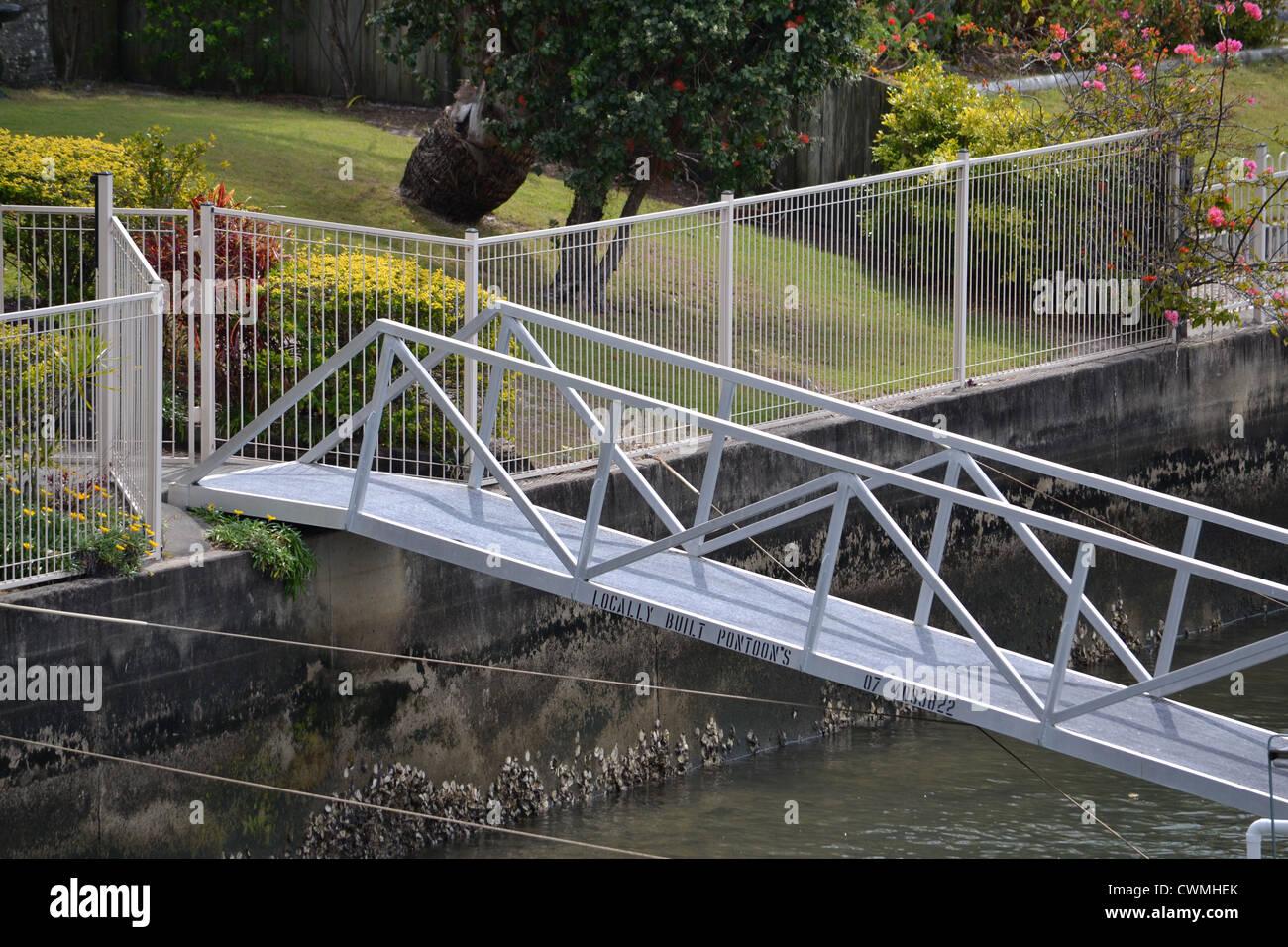 Back fence and steel pontoon walkway - Stock Image