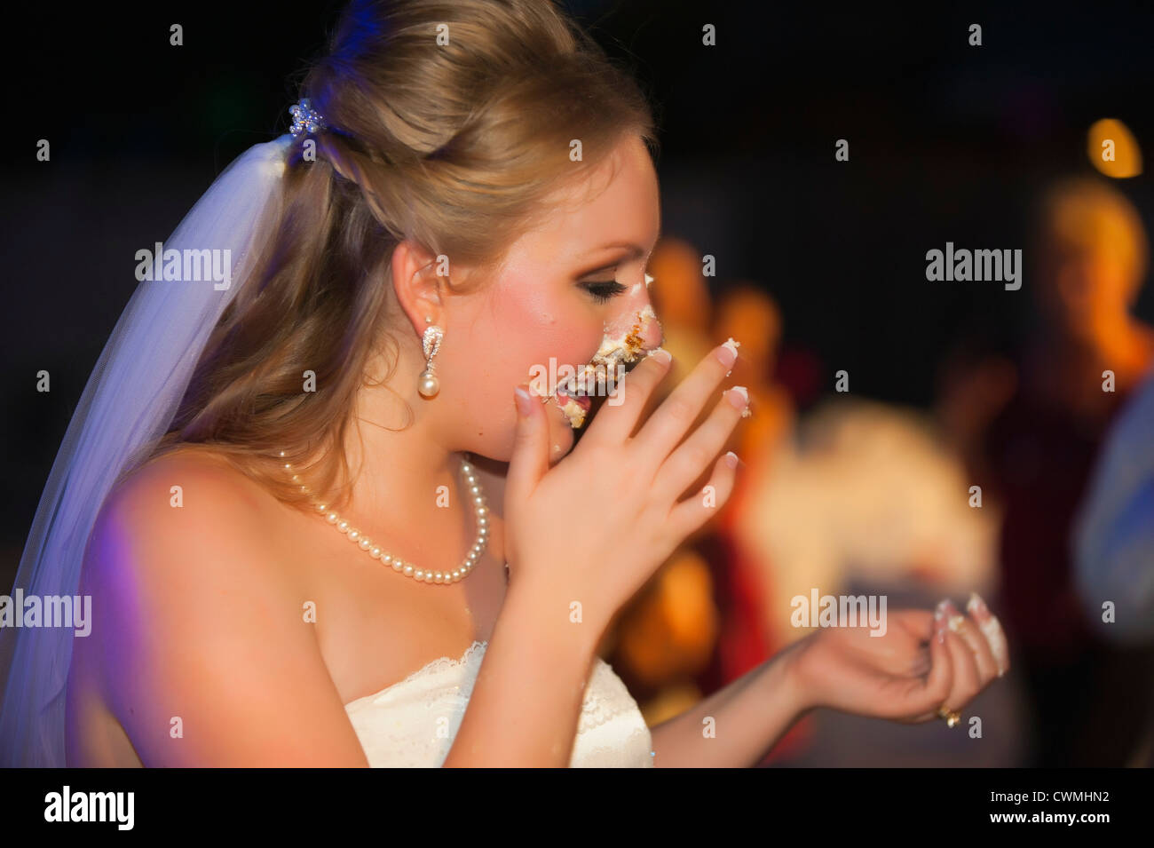 Bride and groom smearing each others faces with icing during a traditional cake cutting ceremony at their American - Stock Image