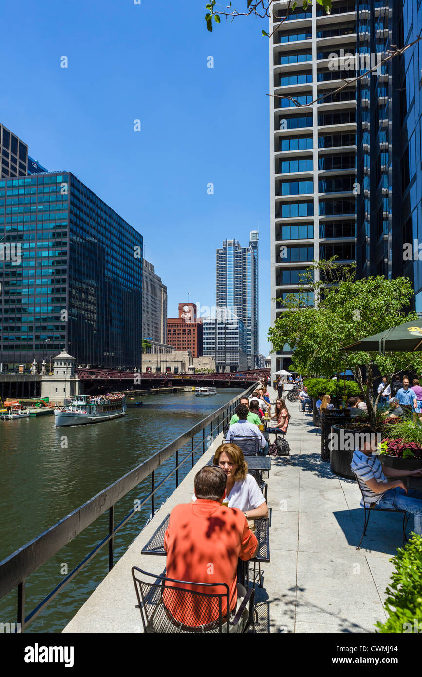 Restaurant terrace overlooking Chicago River with Monroe Street Bridge behind and tour boat on the river, Chicago, - Stock Image