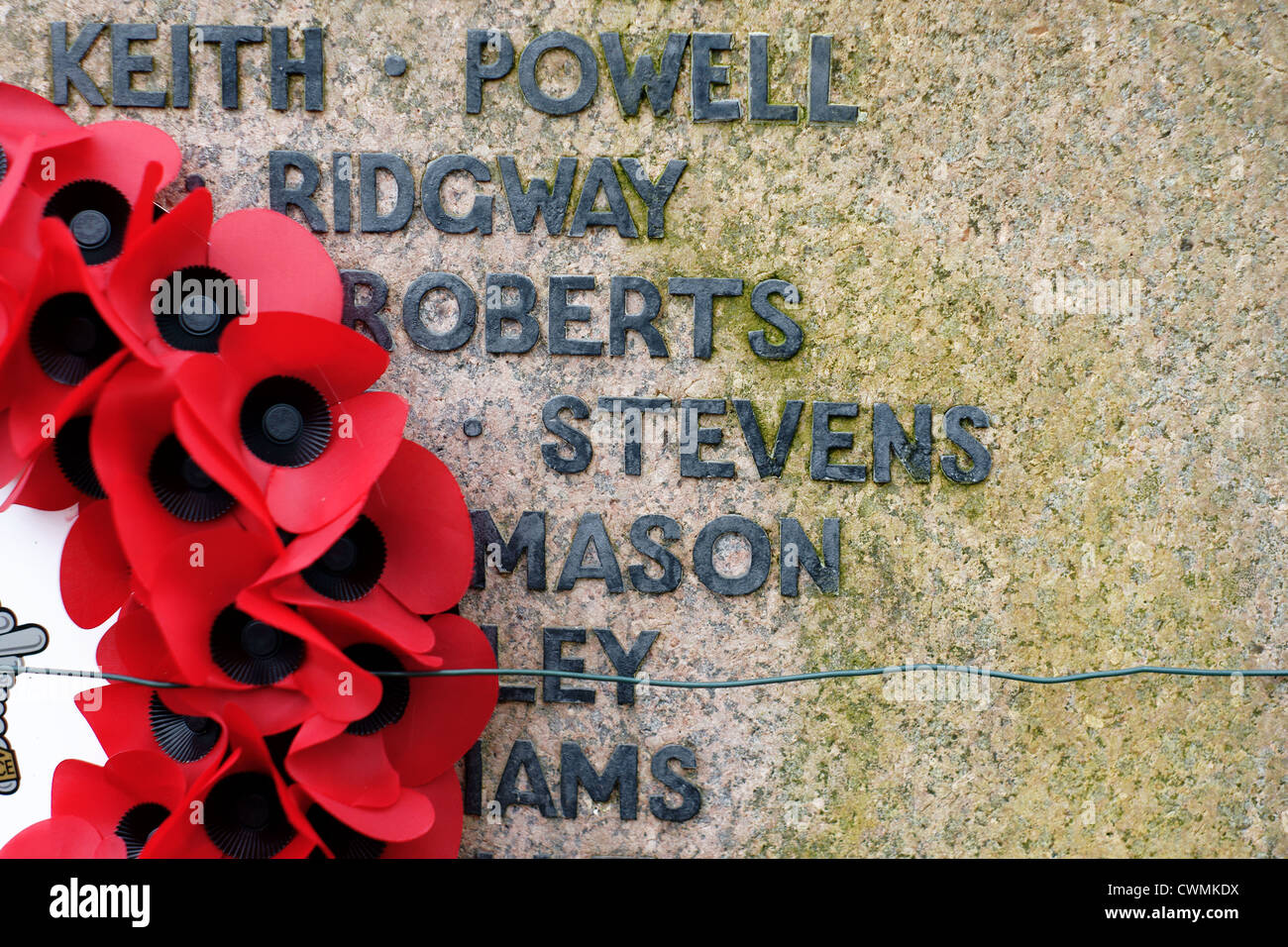 Poppy wreath on a war memorial to commemorate fallen servicemen in past conflicts - Stock Image