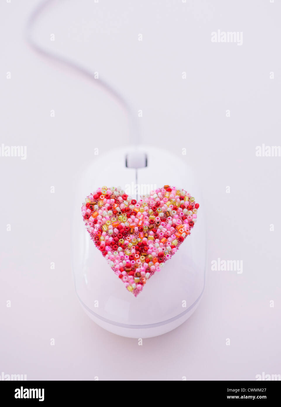Colorful heart on computer mouse - Stock Image