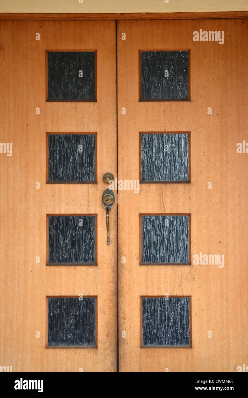 interesting double entry doors of a house with eight glass panels - Stock Image