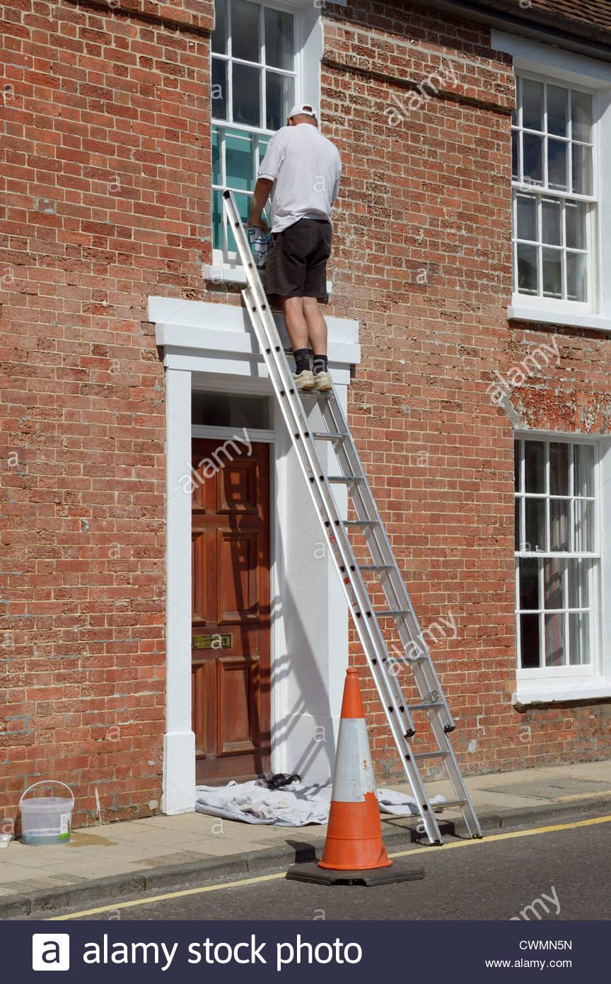 Workman up a ladder decorating sash window, West Street, Wimborne Minster, Dorset, England - Stock Image
