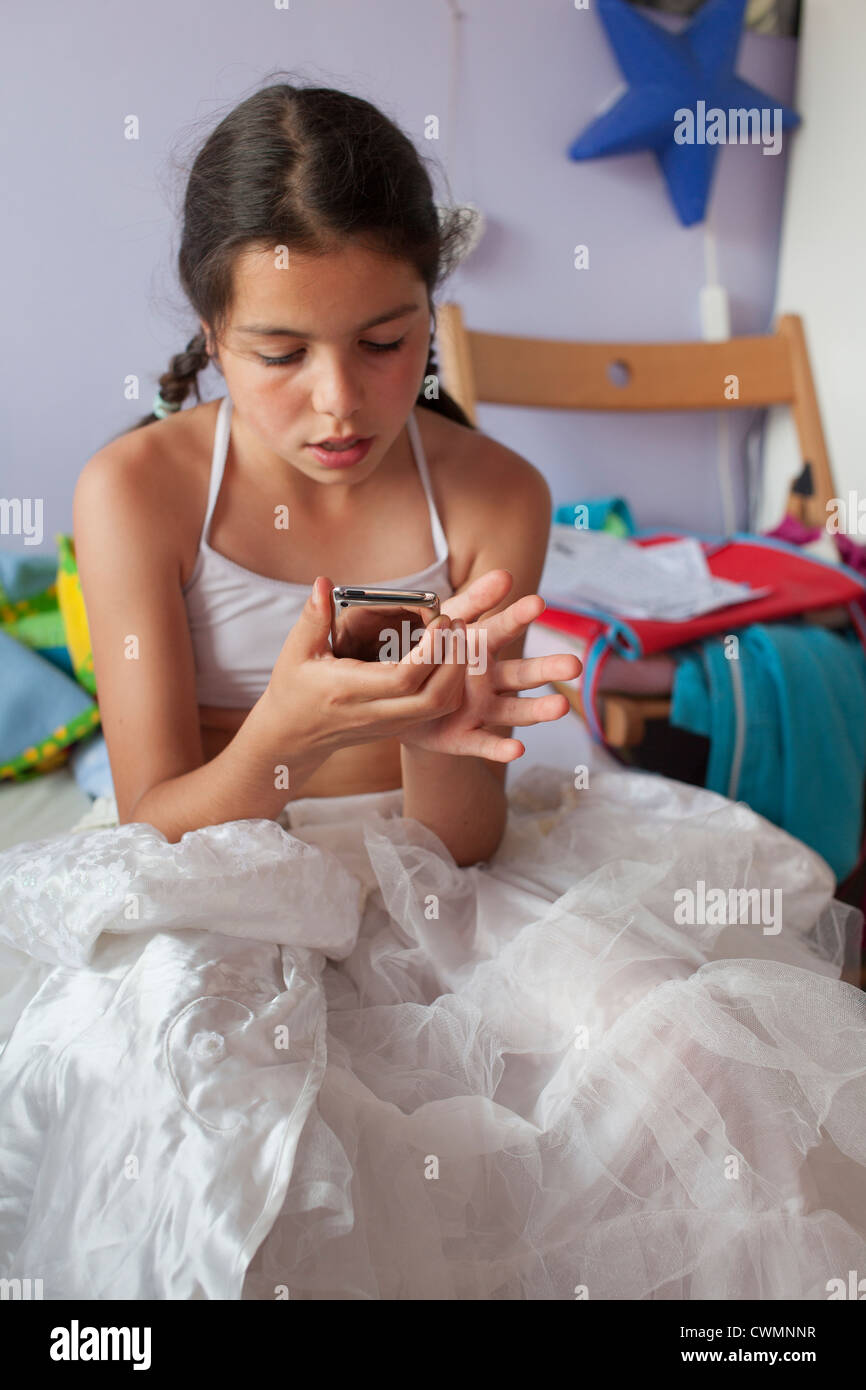 Adolescent girl checks social network site on mobile device - Stock Image