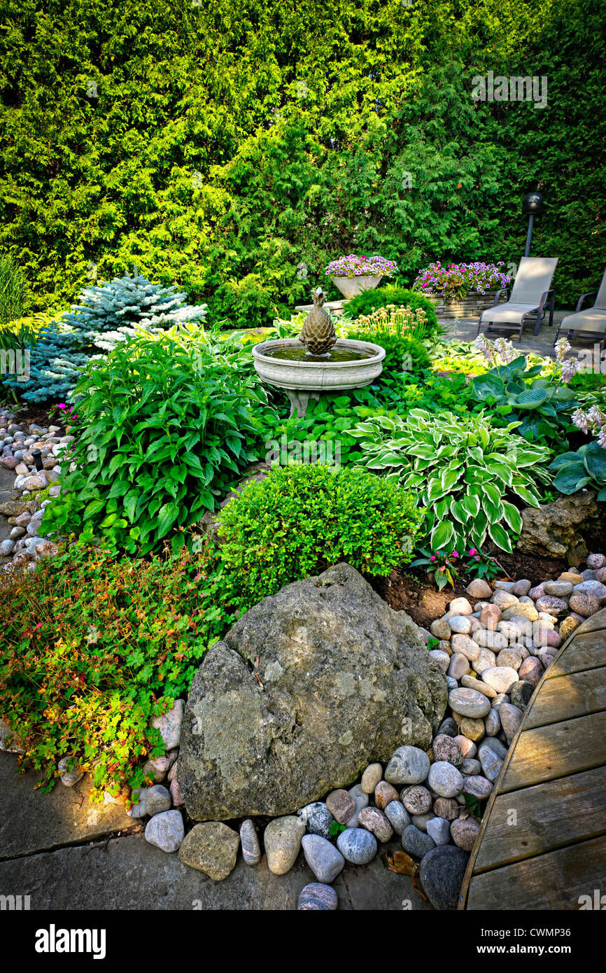 Lush perennial garden with fountain plants and trees - Stock Image
