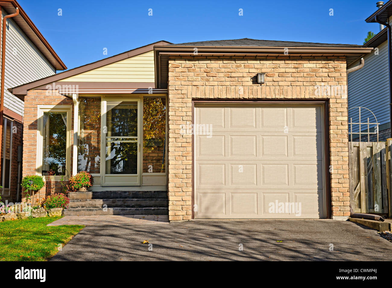 Suburban small bungalow house with single garage - Stock Image