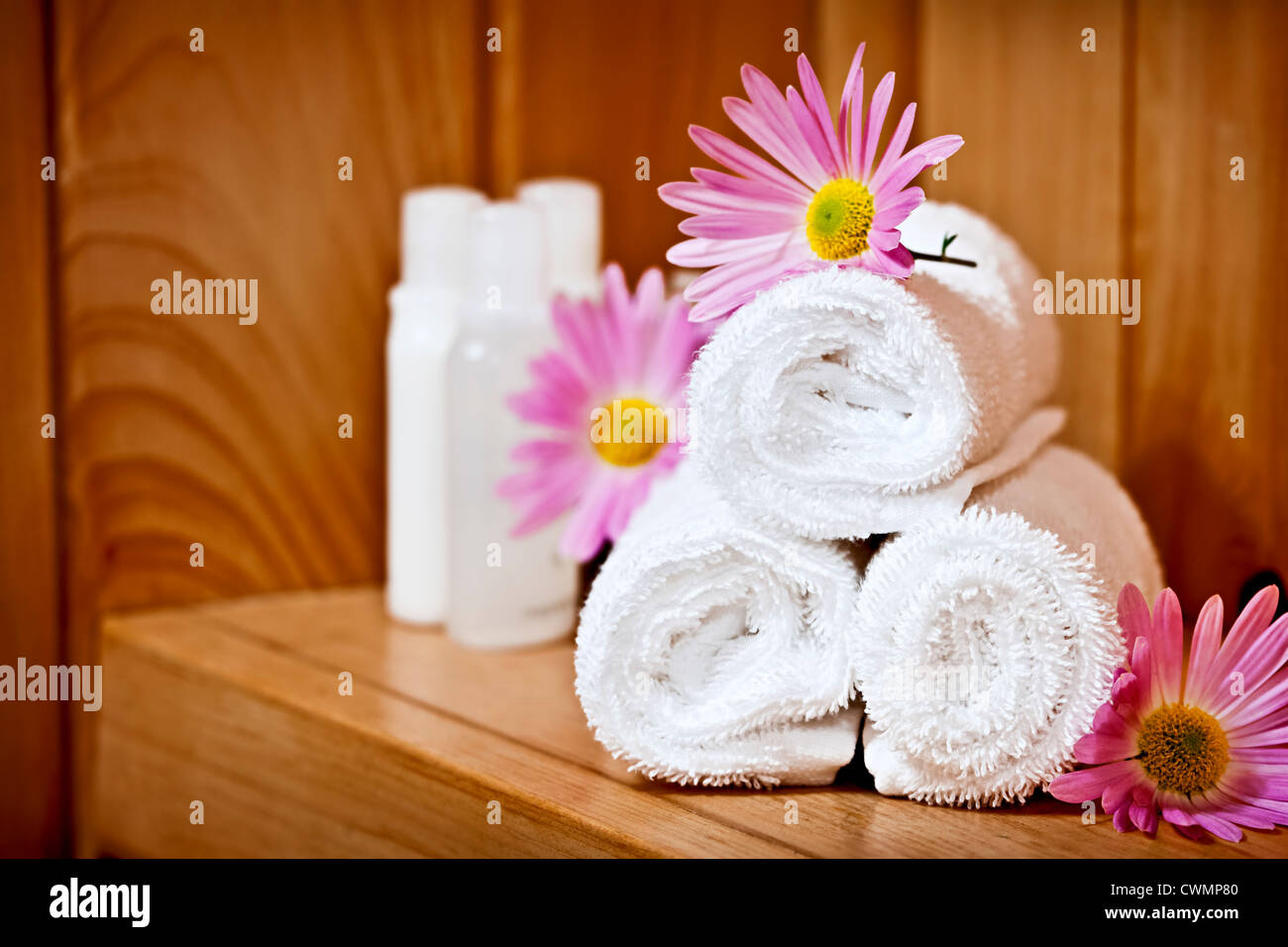 White rolled up spa towels with body care products - Stock Image