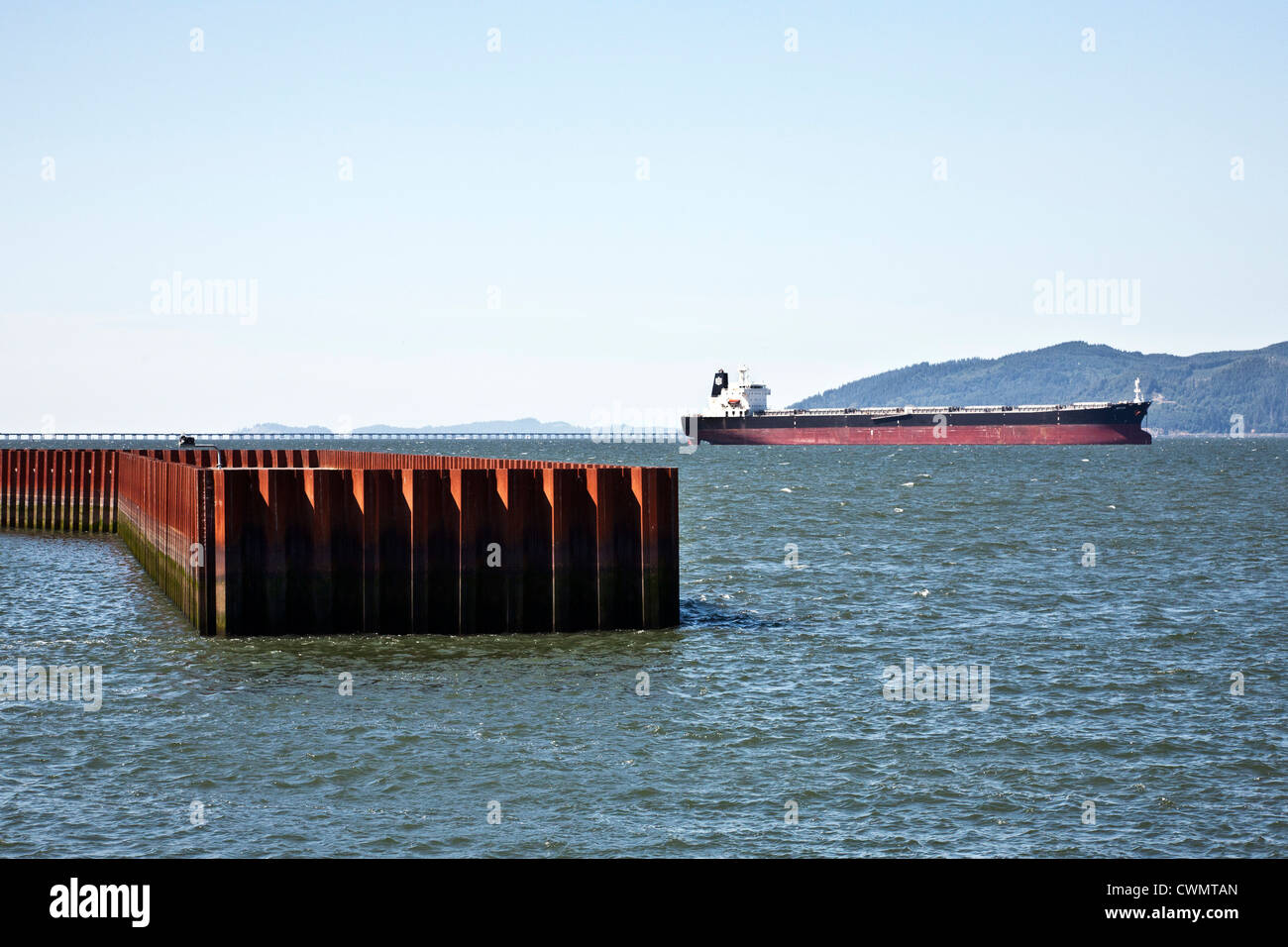 empty container ship anchored inside mouth of mighty Columbia River with steel piling breakwater in foreground Astoria - Stock Image