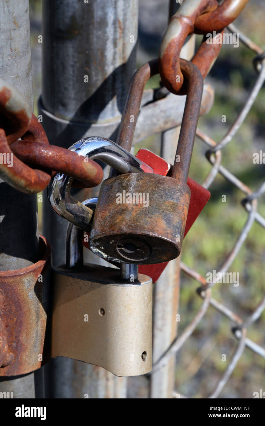 A triple padlocked gate. - Stock Image
