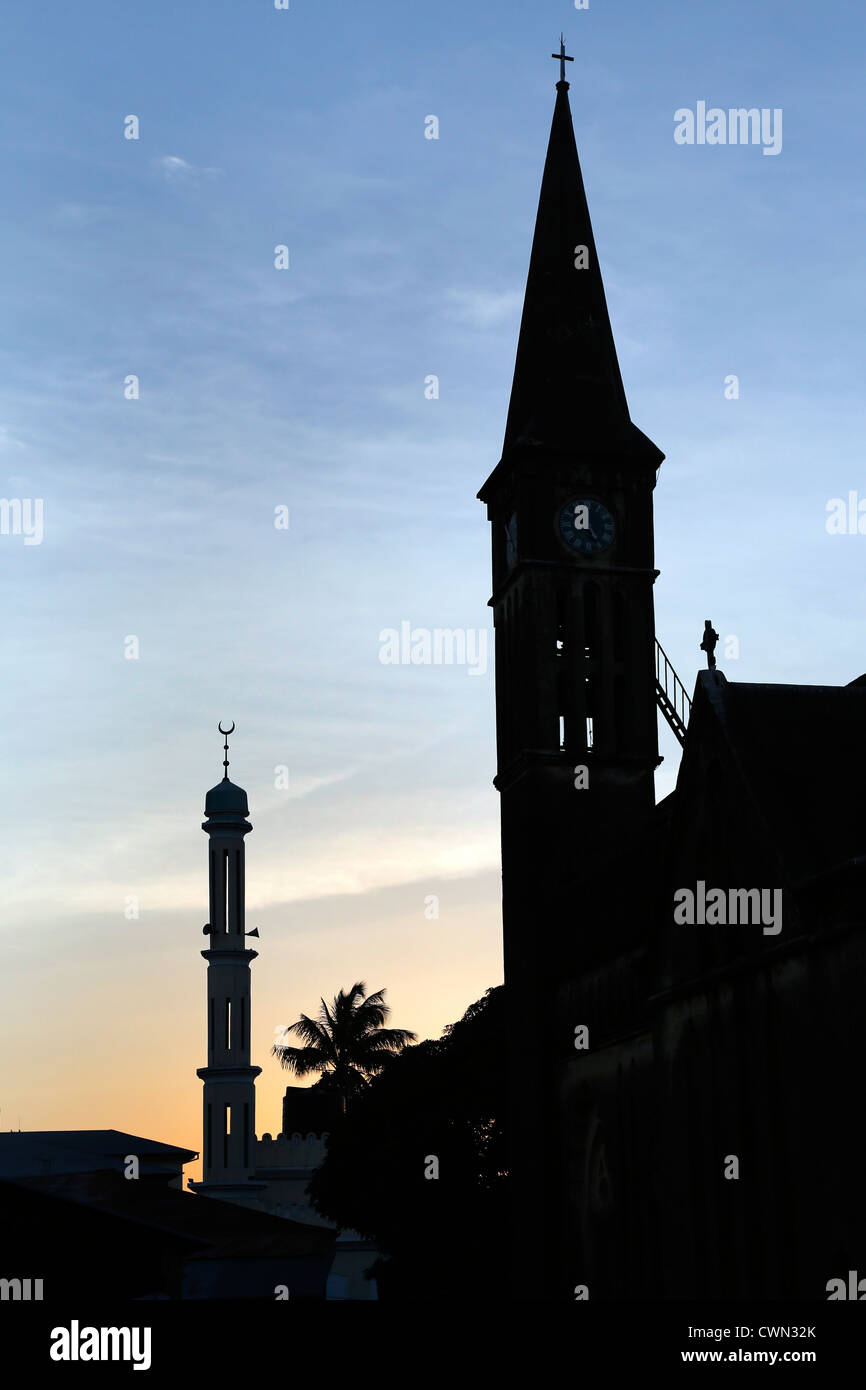 Belltower of the anglican cathedral on the site of the former slave market and Mosque Minaret in Stonetown, Zanzibar, - Stock Image