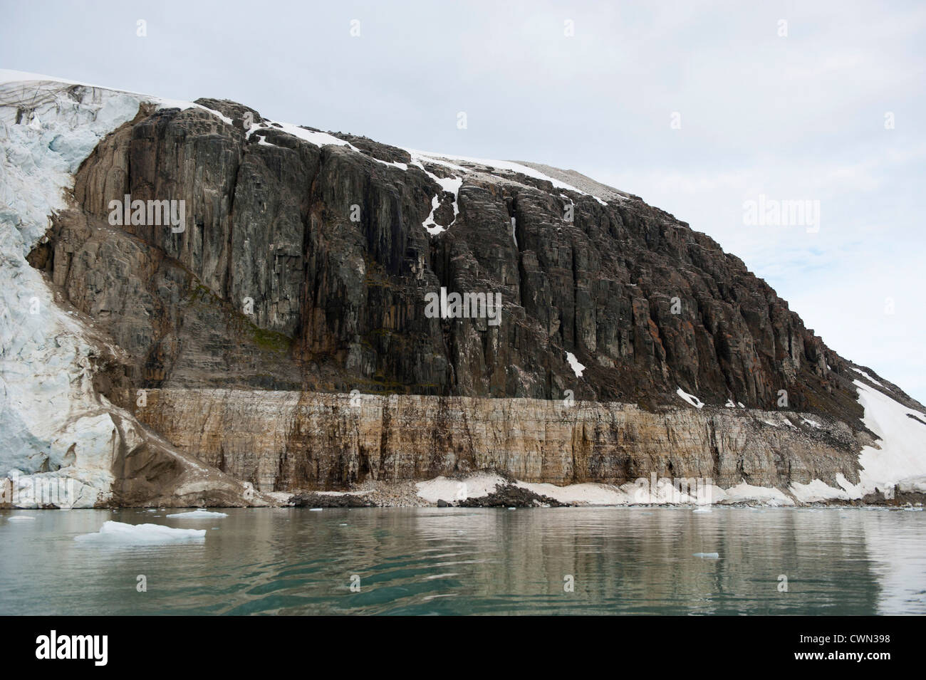 Doloritic intrusion. Limestone at the bottom and top divided by a dolorite sill, Alkefjellet, Spitsbergen, Svalbard, - Stock Image