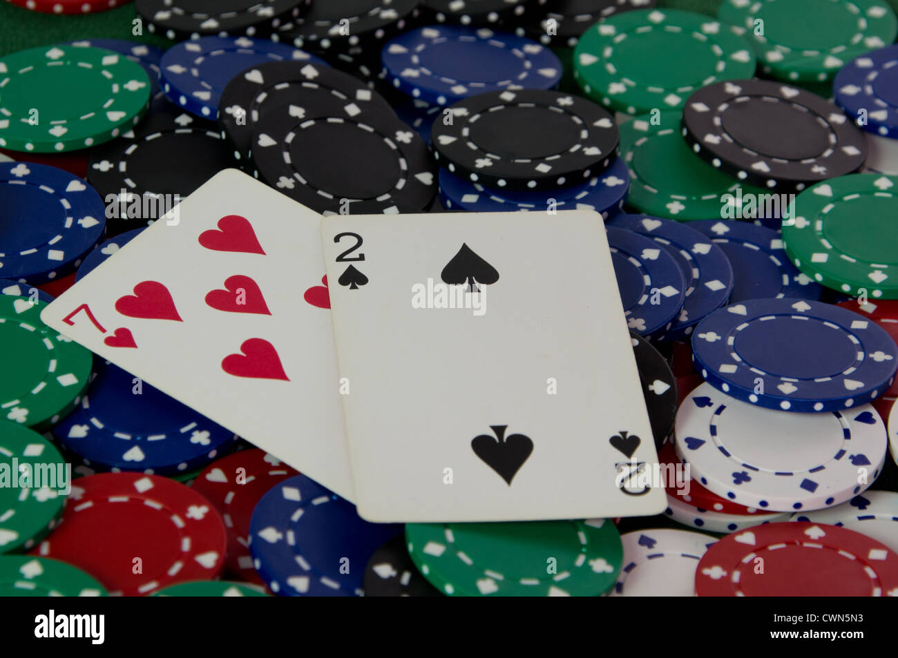 Seven deuce off suit Texas Hold'em Poker hand on a pile of casino chips - Stock Image