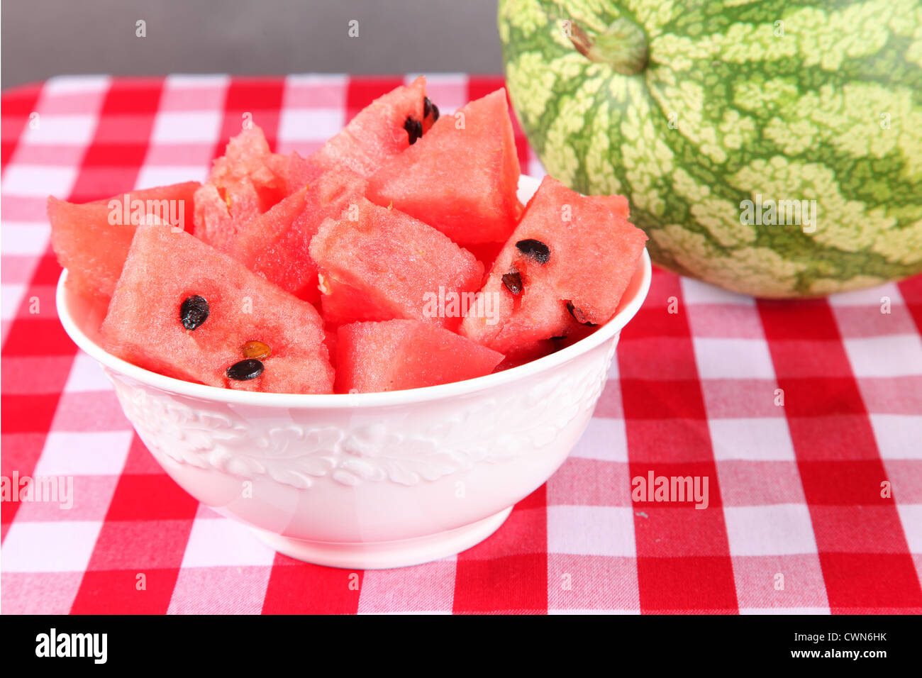 Pieces of fresh cut up watermelon in a white bowl on a gingham tablecloth. - Stock Image