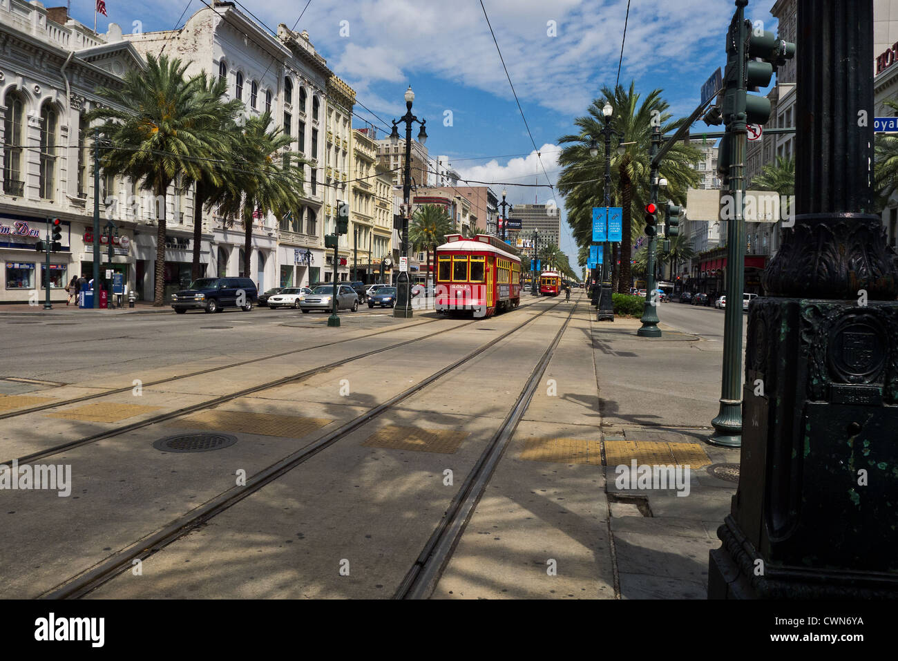 A view of Canal Street in New Orleans looking uptown, showing streetcars, general traffic, palm trees, shops and - Stock Image