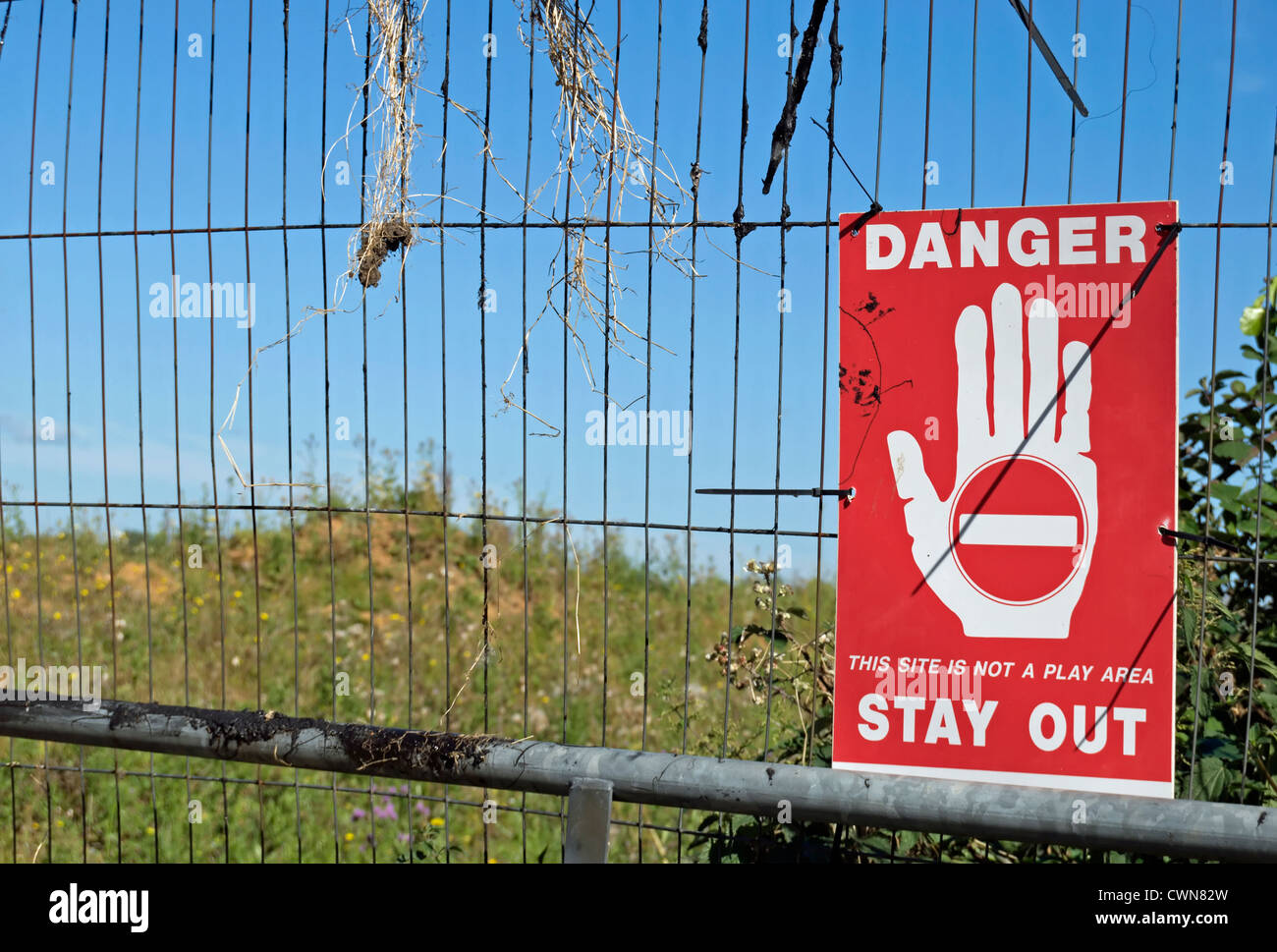 danger stay out sign on a fence adjacent to wasteground in harlington, middlesex, england - Stock Image