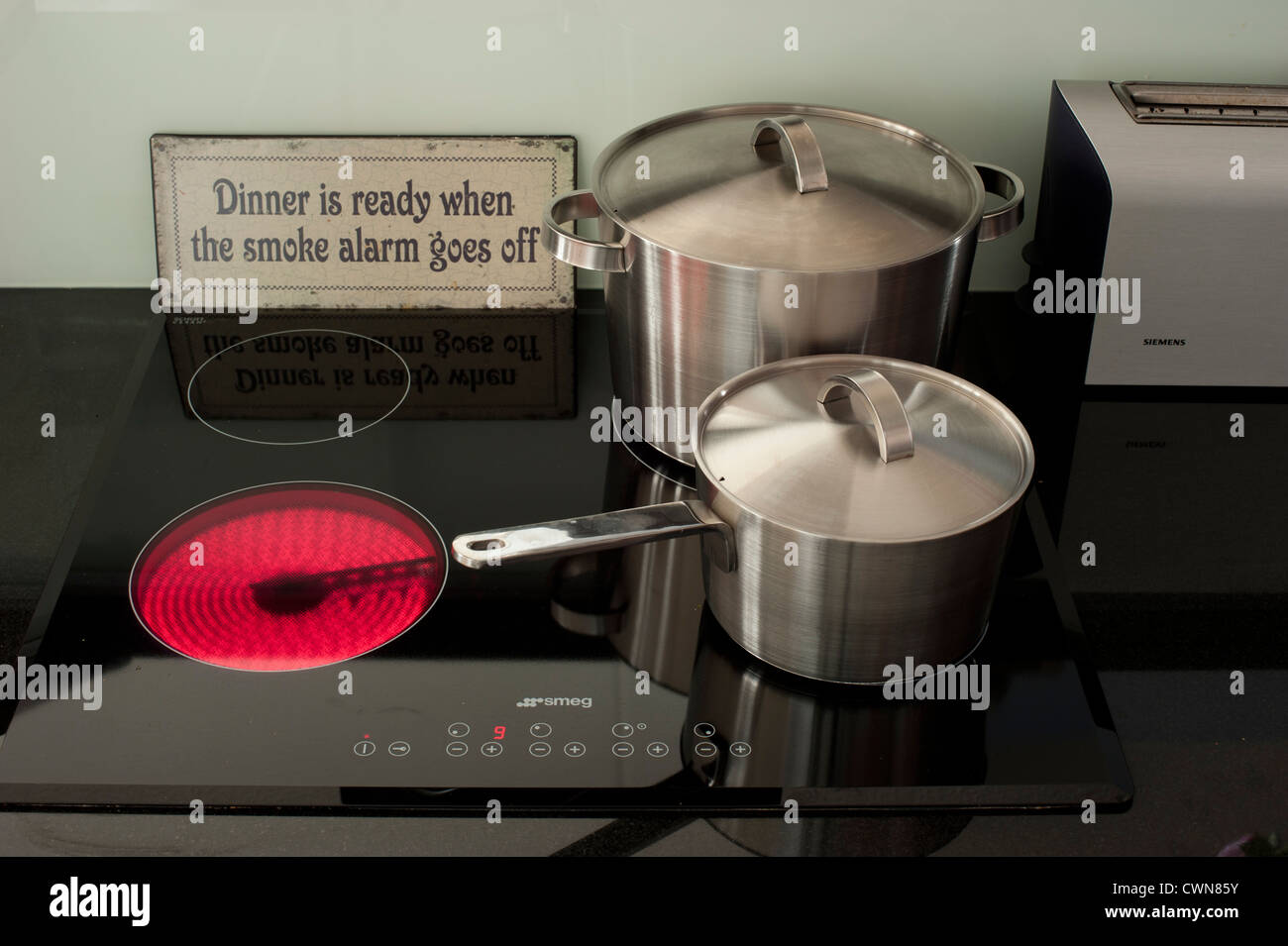 Stainless steel pans next to a burning ceramic cooking stove - Stock Image