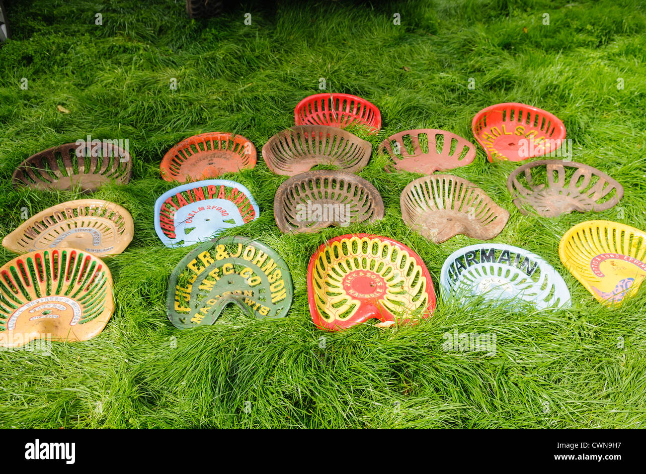 Collection of metal tractor seats from vintage tractors