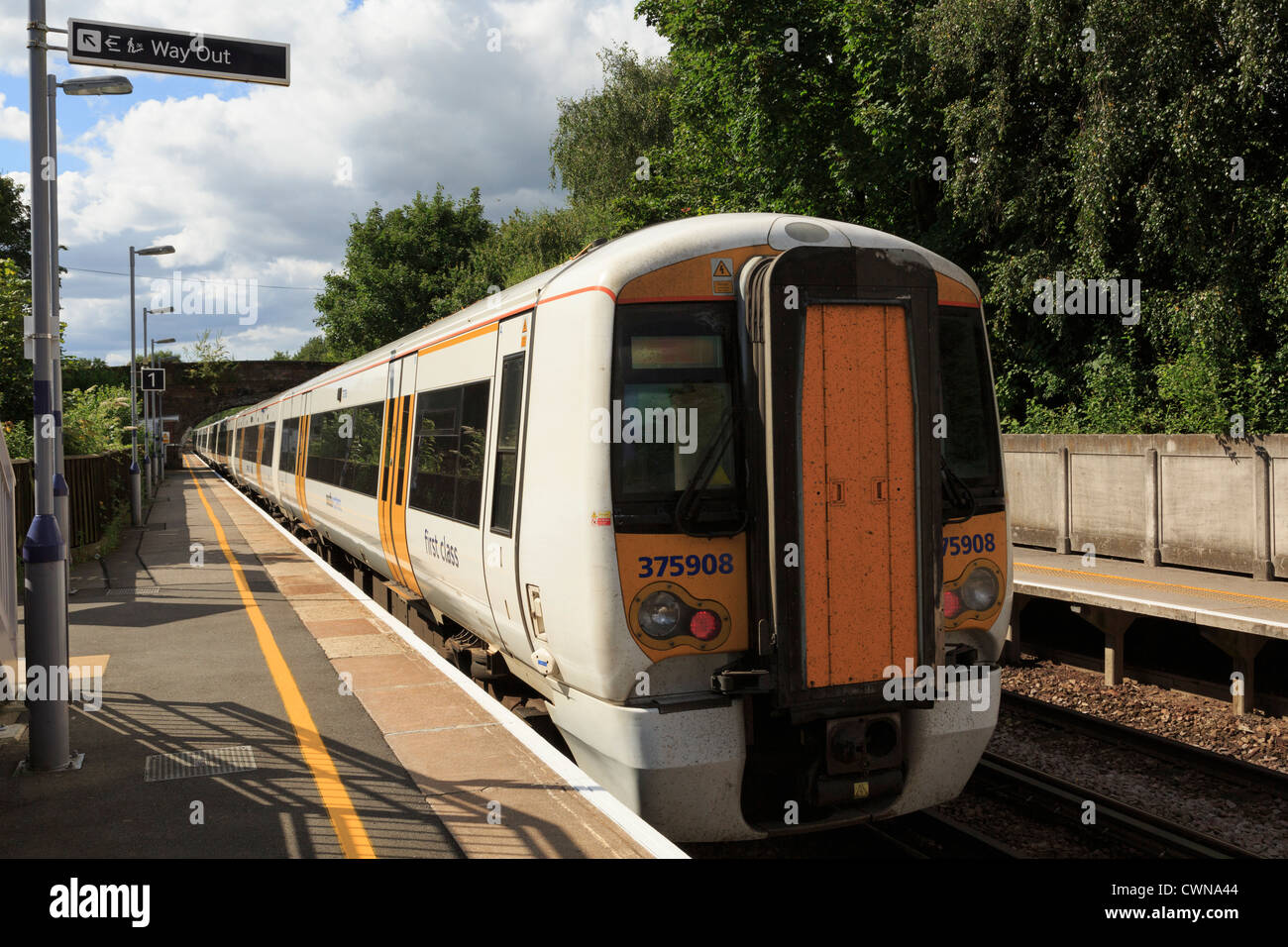 Rear of a London-bound SouthEastern train departing from platform in rural railway station of Pluckley Kent England - Stock Image
