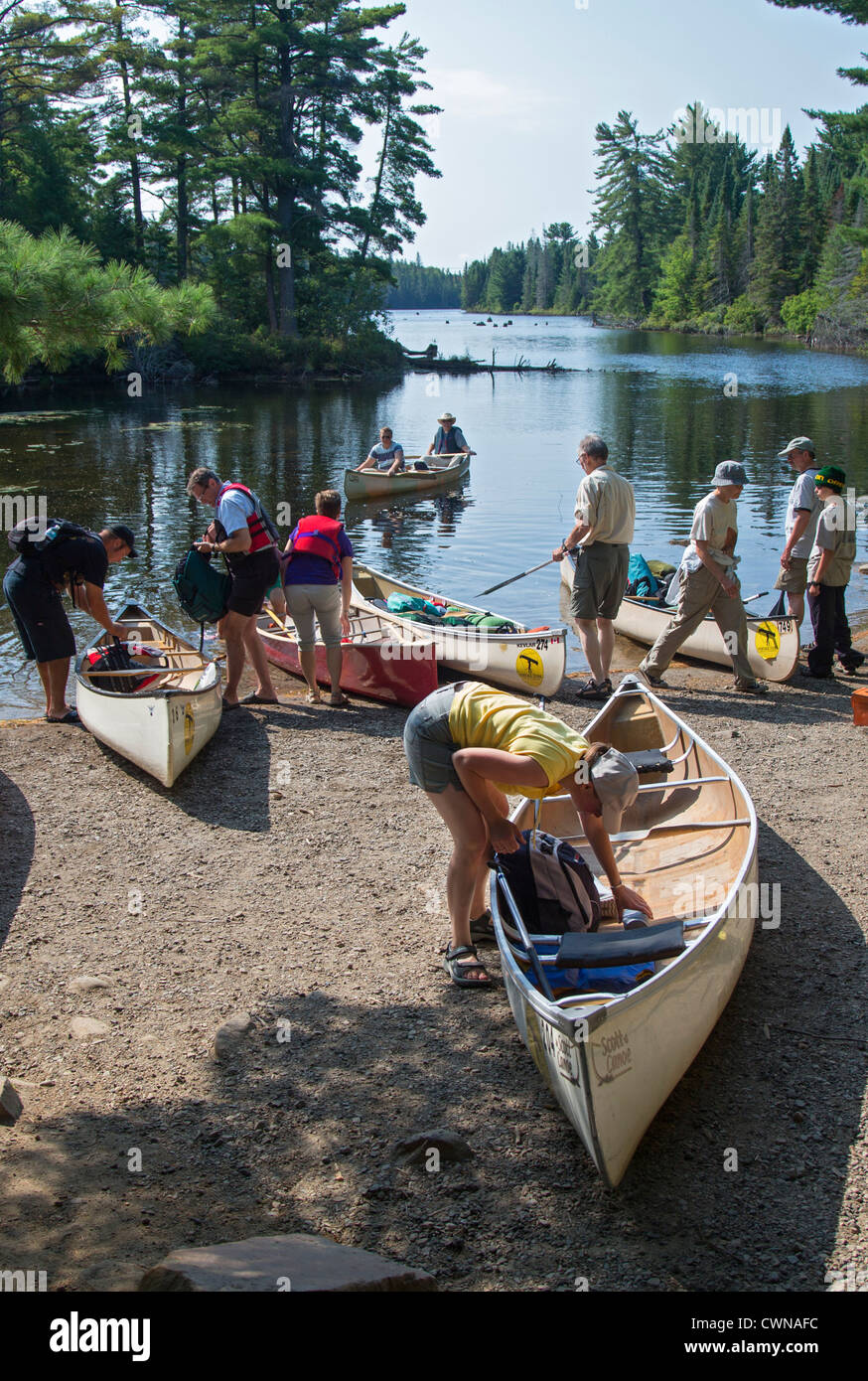 Canoe trippers crowd a landing on Canoe Lake as they prepare to portage their canoes in Algonquin Provincial Park. - Stock Image