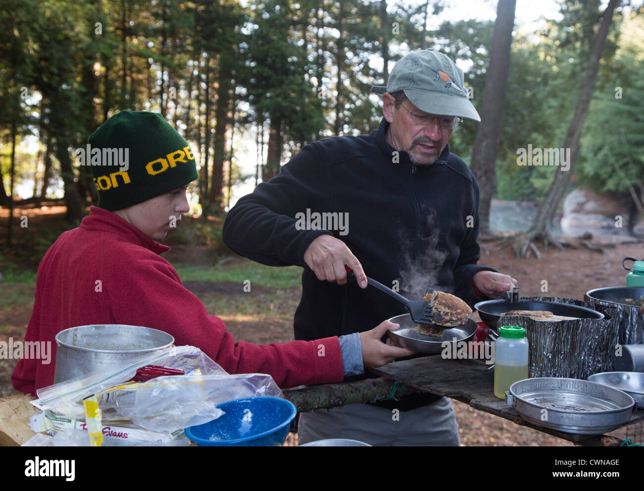 Algonquin Provincial Park, Ontario Canada - John West, 65, cooks pancakes for his son Joey, 13, during a canoe trip. - Stock Image