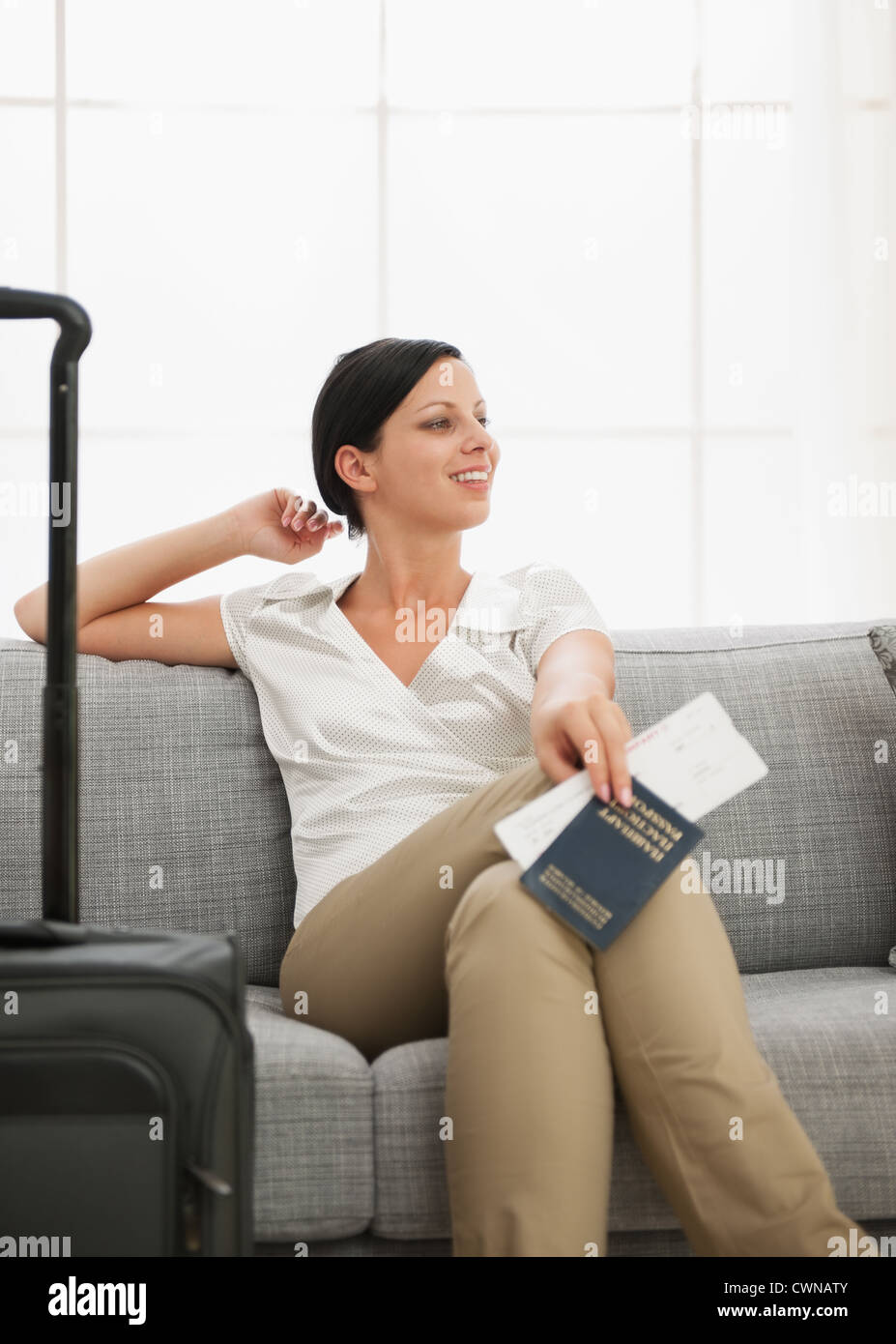 Dreaming young woman with bag holding passport and air ticket - Stock Image