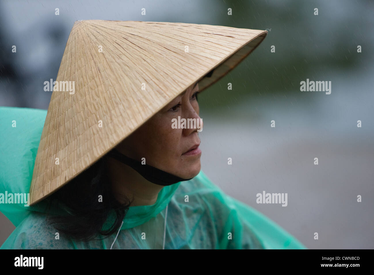 Woman in the rain from Hoi An - Stock Image