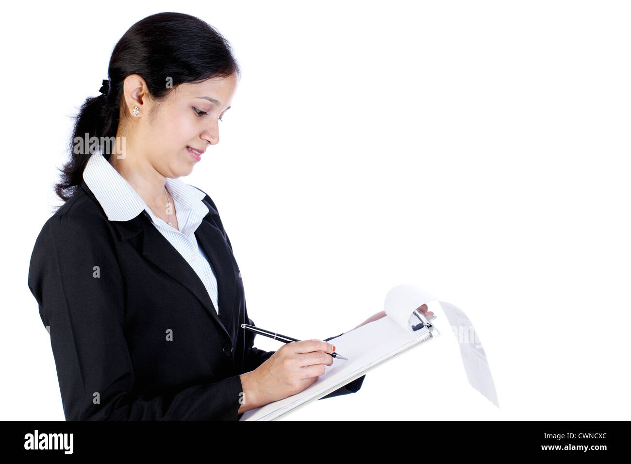 Beautiful business woman holding a clipboard and writing on white background - Stock Image