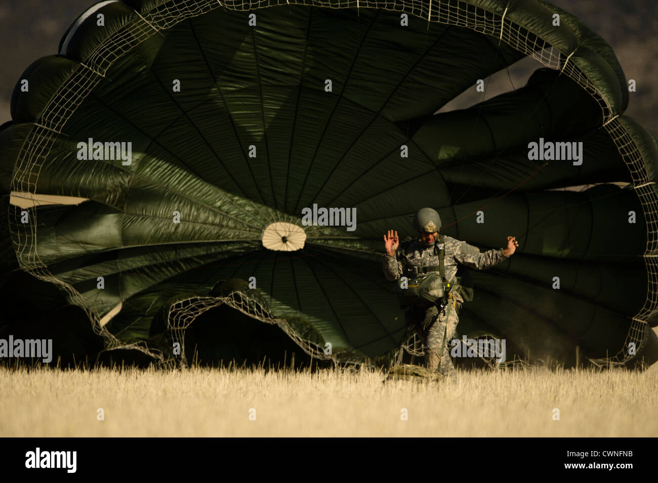 A US Army soldier from the Utah National Guard prepares to pack his parachute after a static line jump March 15, 2012 in Fairfield, Utah. Stock Photo