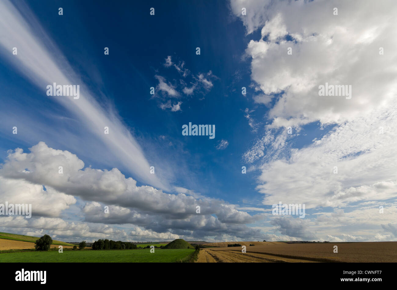 chalk downland with cirrus and cumulus clouds above farrnland Silbury Hill Wiltshire - Stock Image