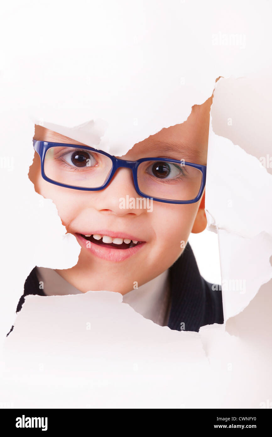 Curious kid in spectacles looks through a hole in white paper - Stock Image
