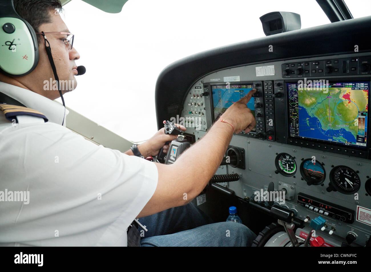 Pilot in the cockpit at the controls of a Cessna Caravan light aircraft plane, Tanzania, Africa - Stock Image