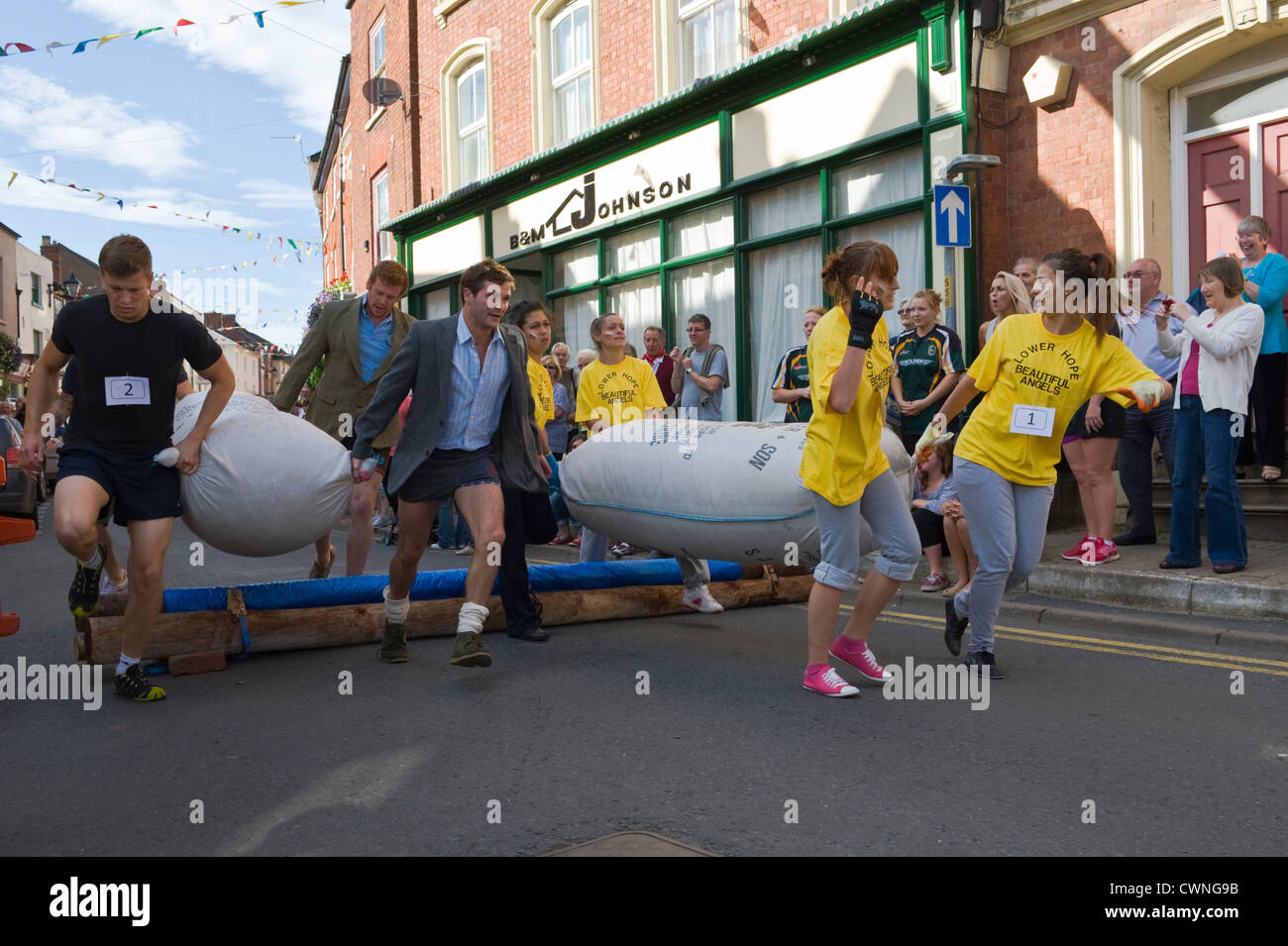 Competitors jump the hurdle in the annual World Championship Hop Pocket Race at Bromyard Herefordshire England UK - Stock Image