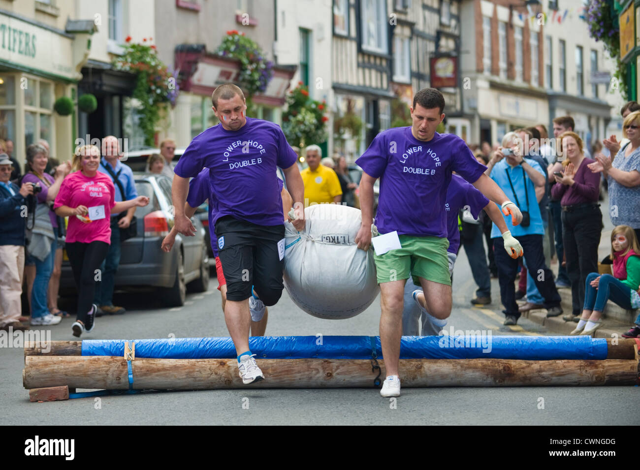 East European men's team jump the hurdle in the annual World Championship Hop Pocket Race at Bromyard Herefordshire - Stock Image