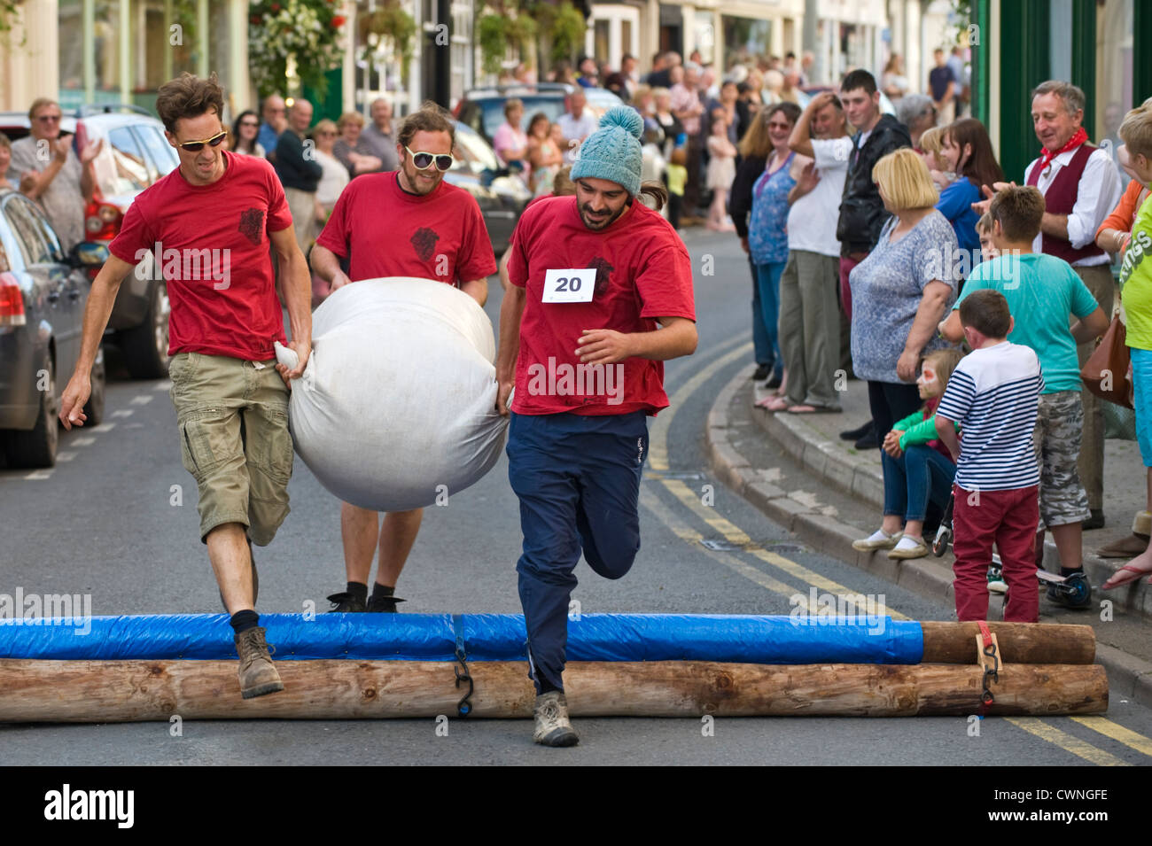 Local men's team jump the hurdle in the annual World Championship Hop Pocket Race at Bromyard Herefordshire - Stock Image