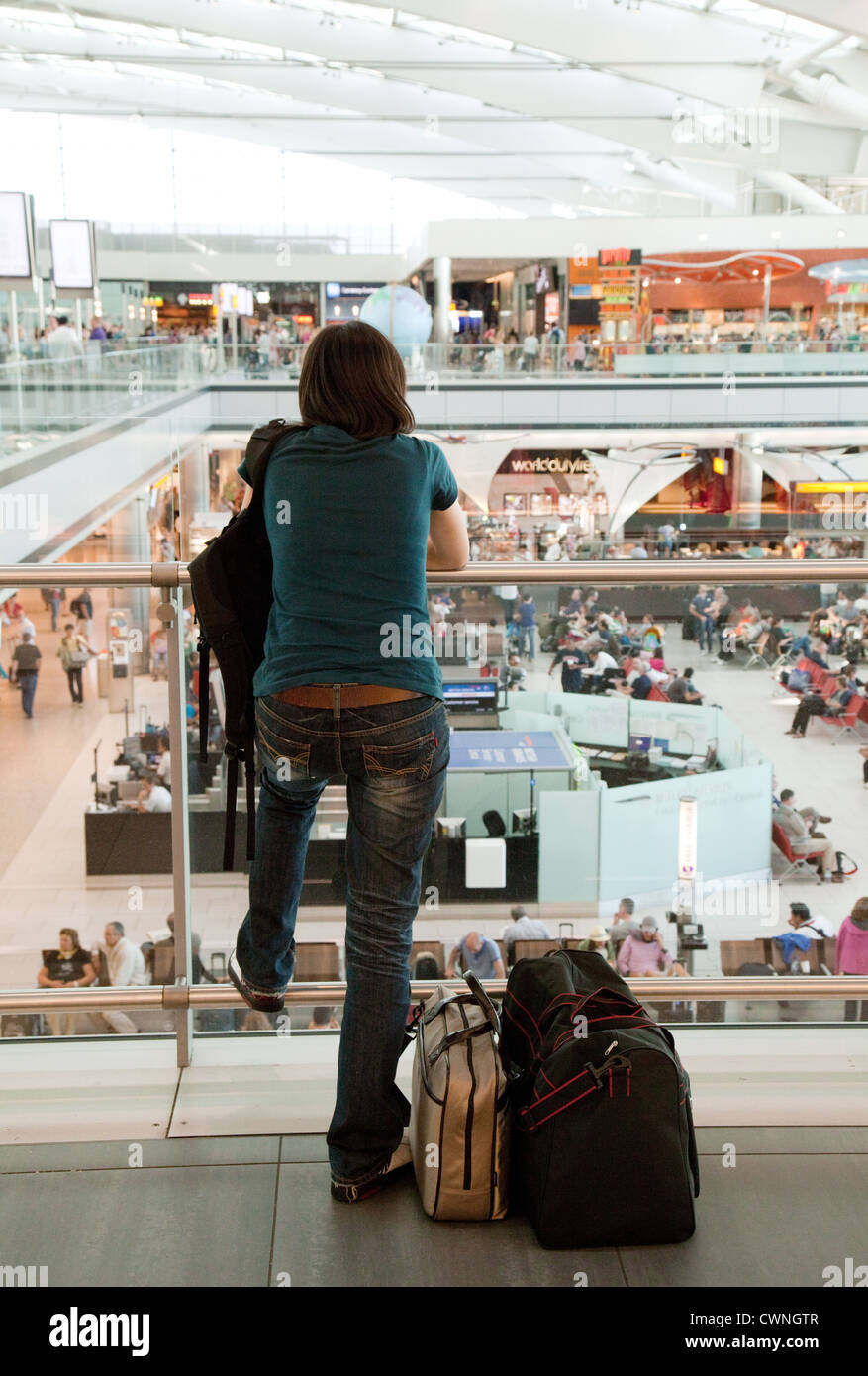 A traveller looking over Terminal 5 departure lounge, Heathrow airport, london UK - Stock Image