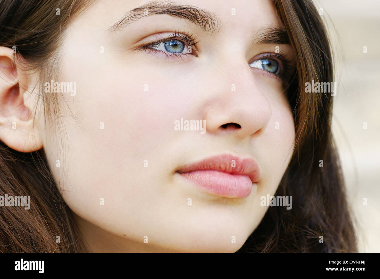 Portrait of s beautiful hopeful or pensive young woman with fair skin and light blue and green eyes, simple and - Stock Image