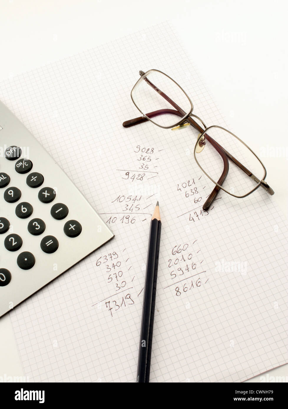 Addition of a written paper, a calculator and pen. - Stock Image