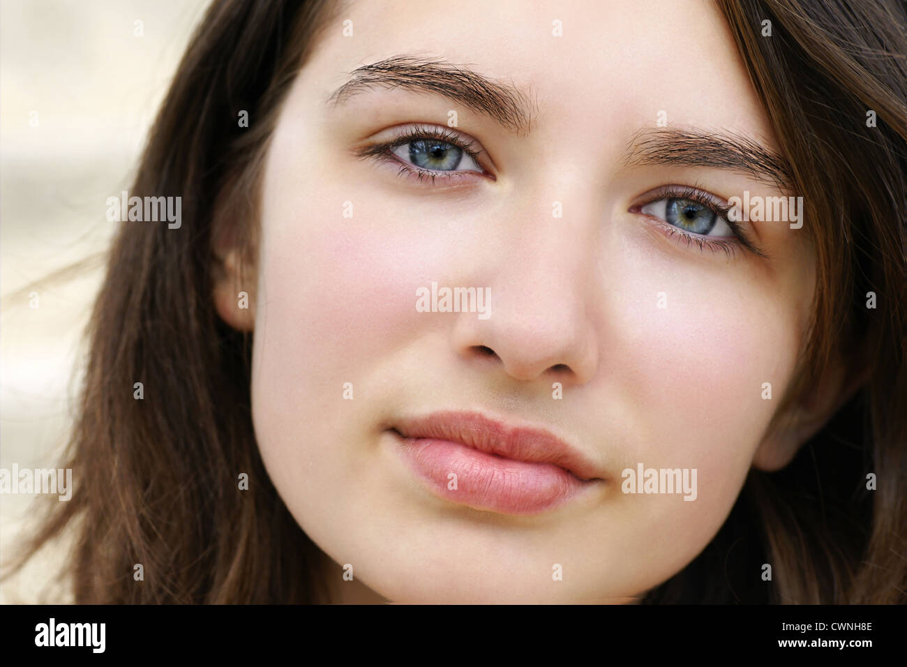 Portrait of serious beautiful fair skin young woman with pale blue eyes - Stock Image