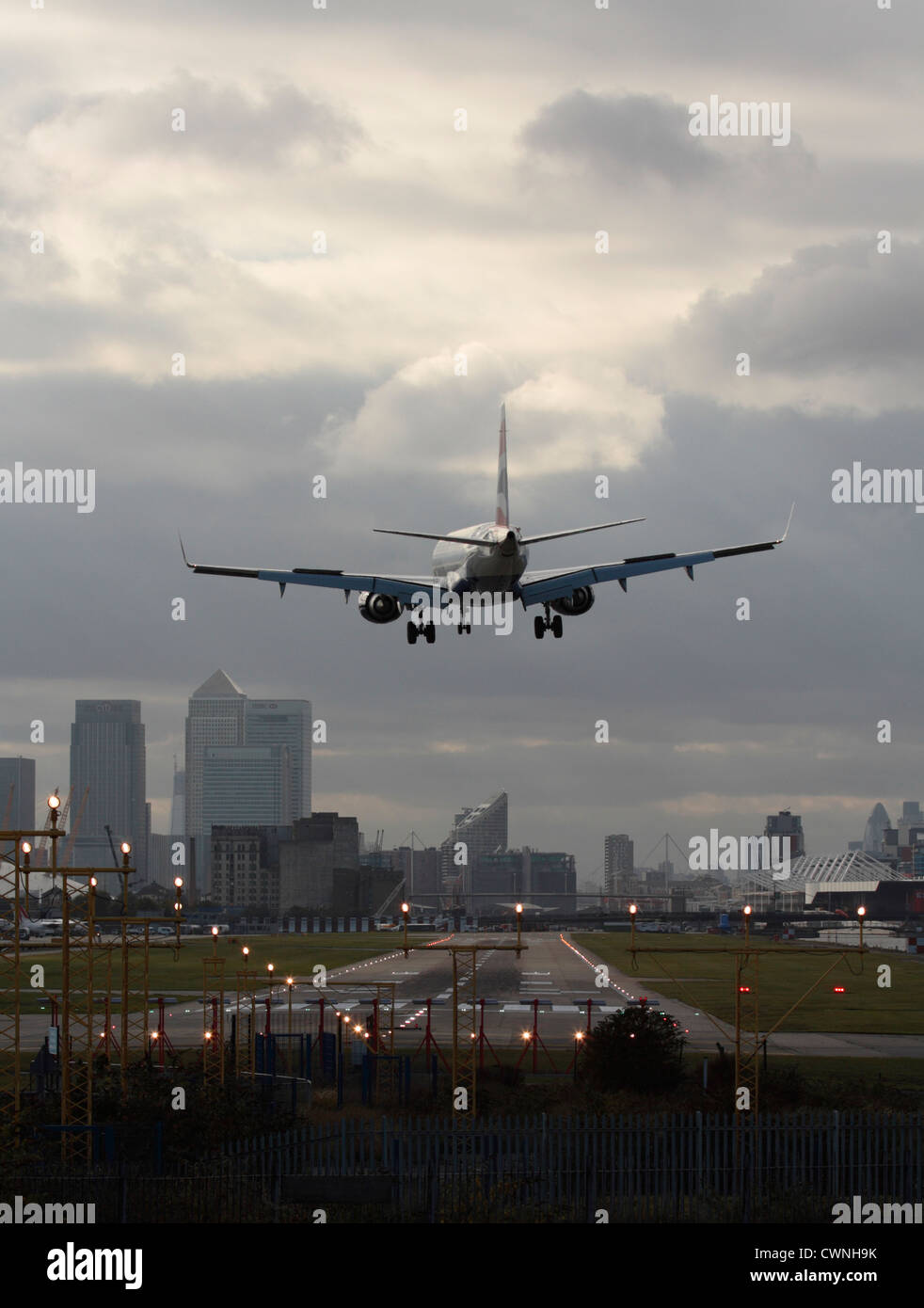 Jet plane landing at London City Airport, with the runway in sight and the financial district visible in the background. - Stock Image