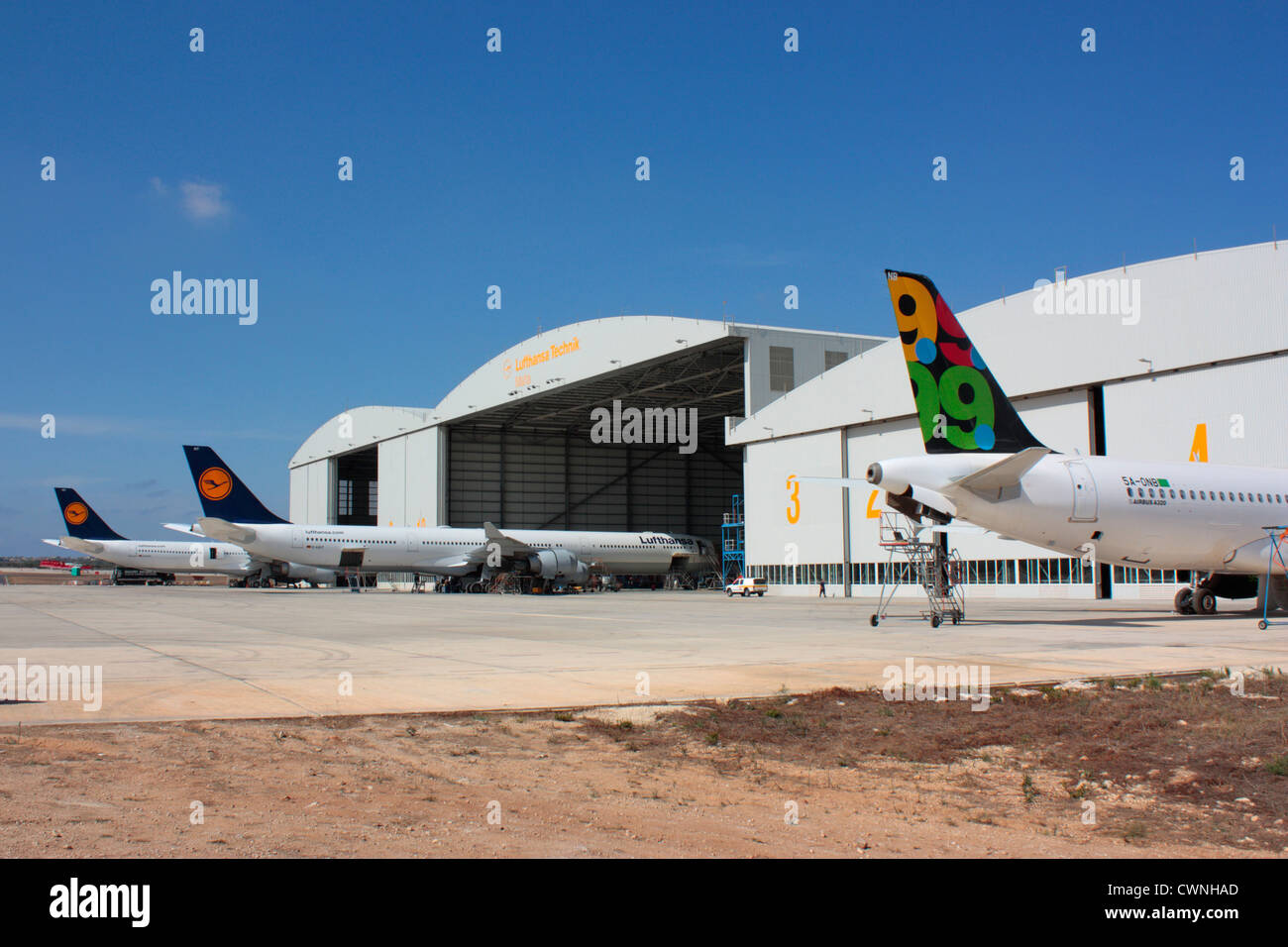 Lufthansa Technik Malta aircraft maintenance hangars with jet planes undergoing overhaul - Stock Image