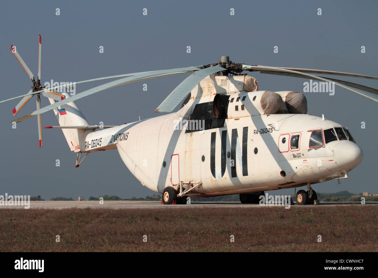 Mil Mi-26 heavy transport helicopter parked on the ground and bearing partially painted out UN titles - Stock Image