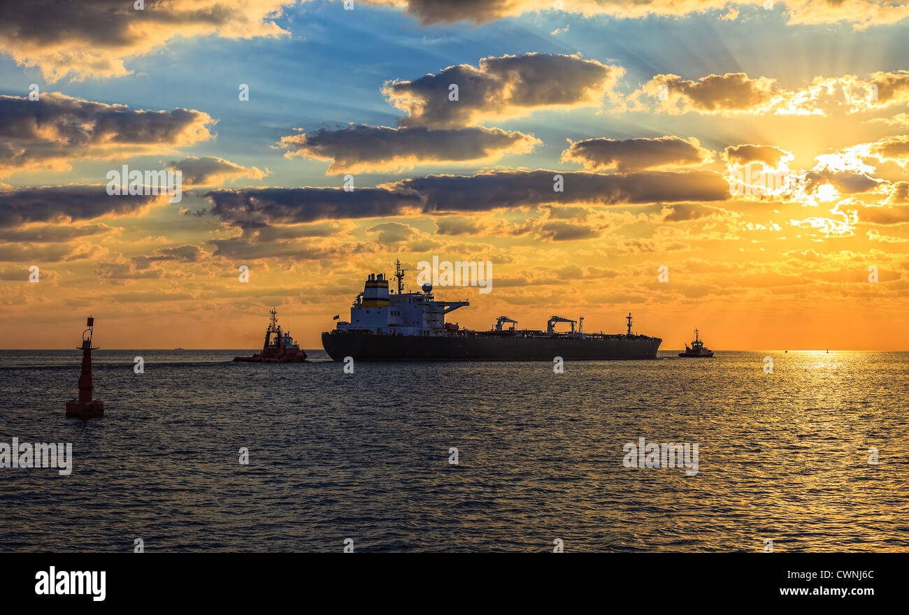 Solar Convoy - Tanker at sunset putting out to sea. - Stock Image