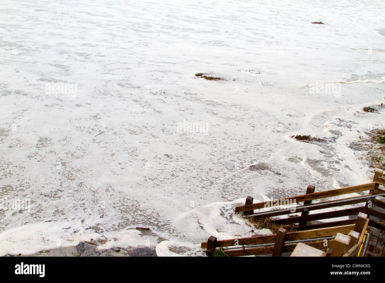 The waves crash on the shore flooding the stairs at high tide on Carmel Beach , California. - Stock Image