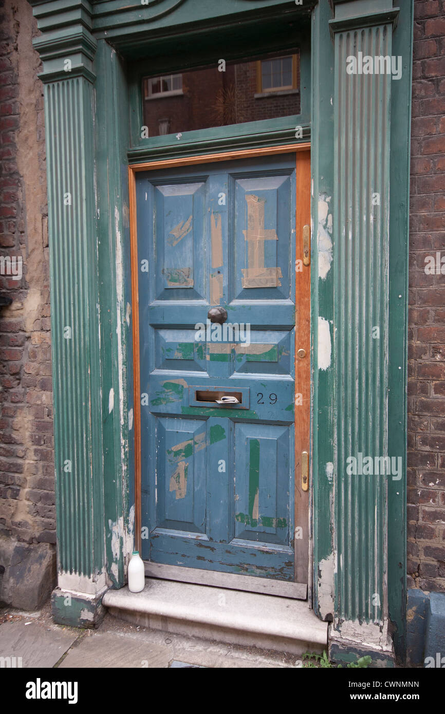 An Old Front Door With Milk Bottle And Peeling Paint Near Brick Lane