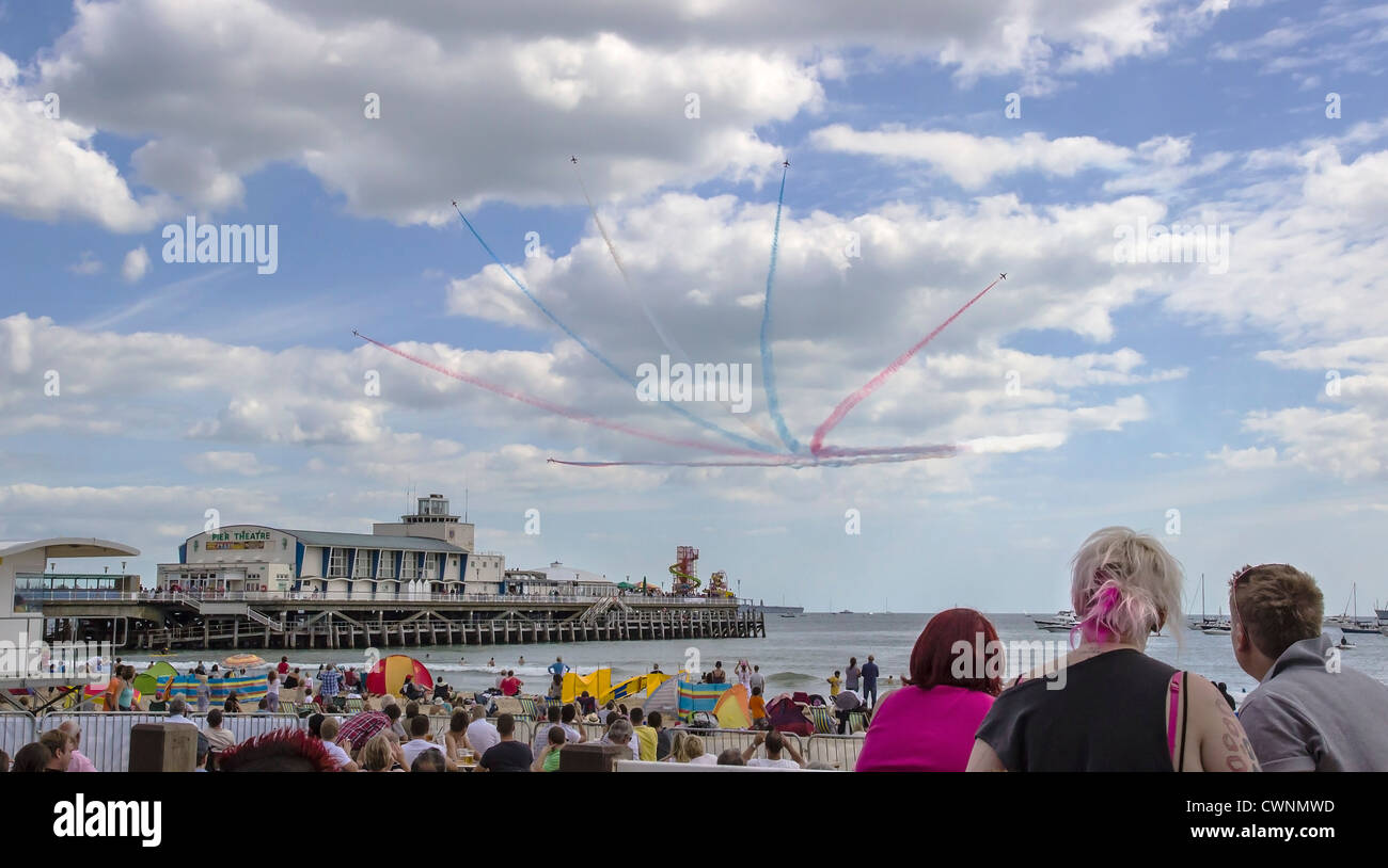 Red Arrows Aerobatic Team flying over Bournemouth Pier with watching crowds on West Beach during the annual Air - Stock Image