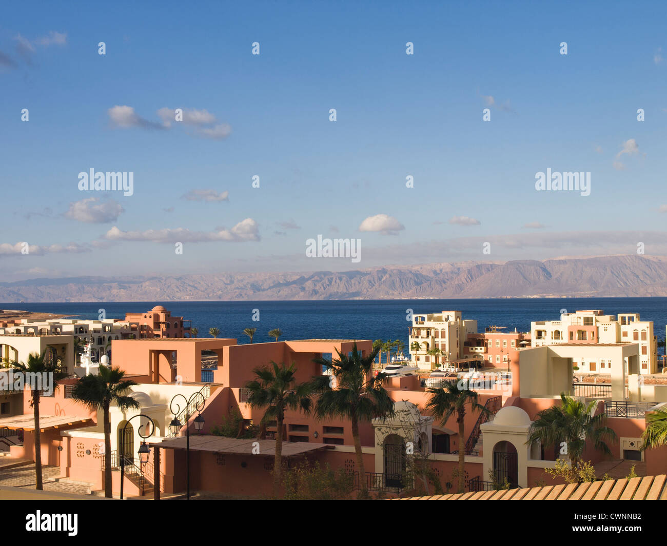Over the rooftops in Tala Bay resort south of Aqaba Jordan you can see the Red Sea and across to Sinai and Egypt - Stock Image