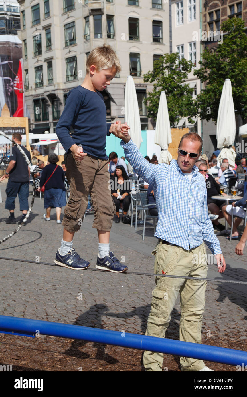 Young boy balancing and tightrope walking on a wire with a firm grip in his father's hand at the pedestrian - Stock Image