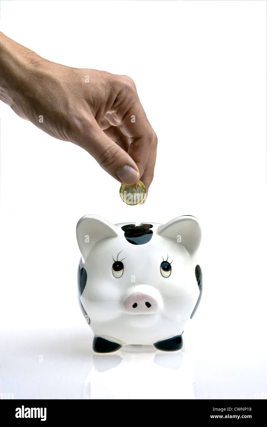 Coin being dropped into a piggy bank - Stock Image