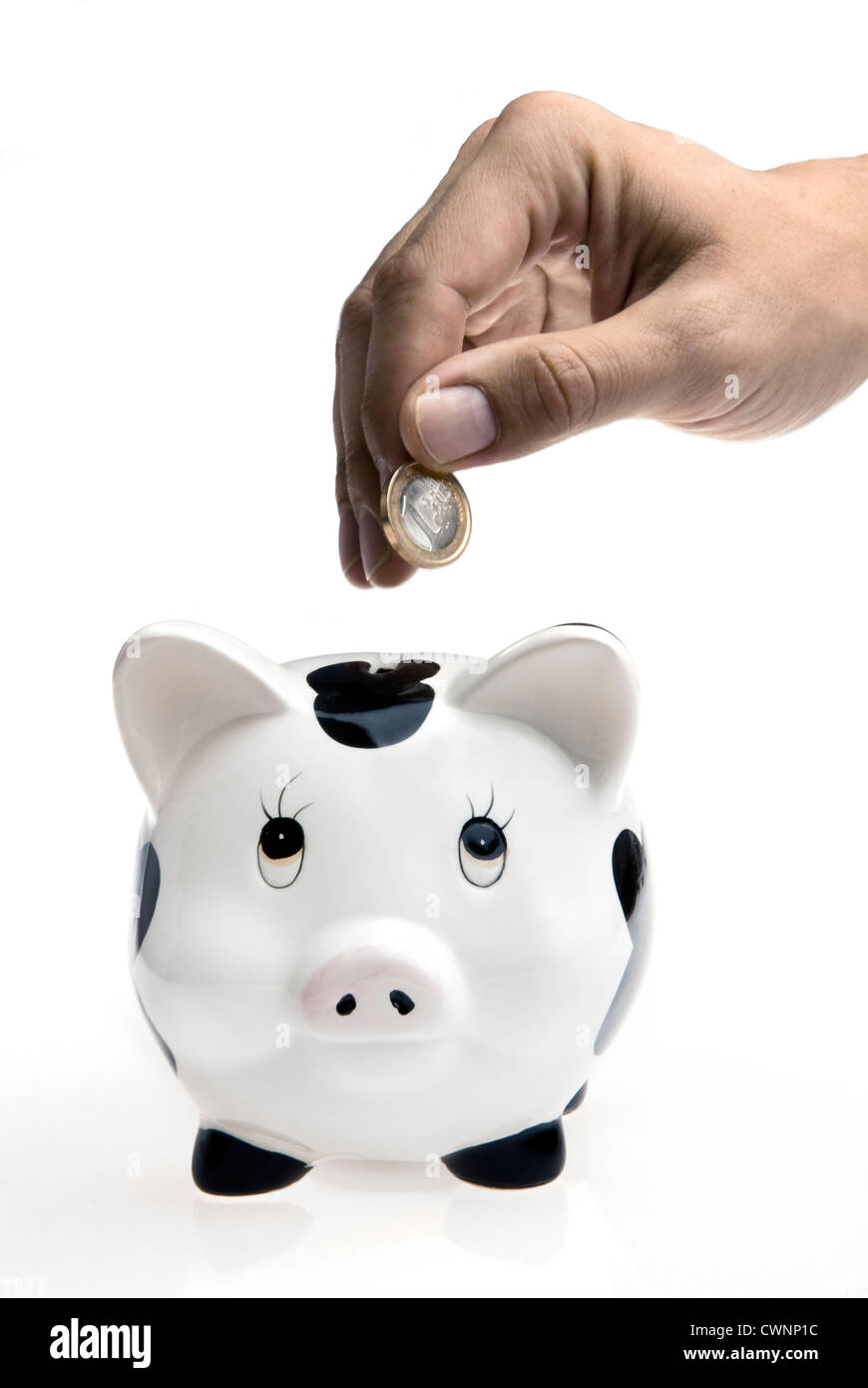 Coin being dropped into a piggy bank on white background - Stock Image