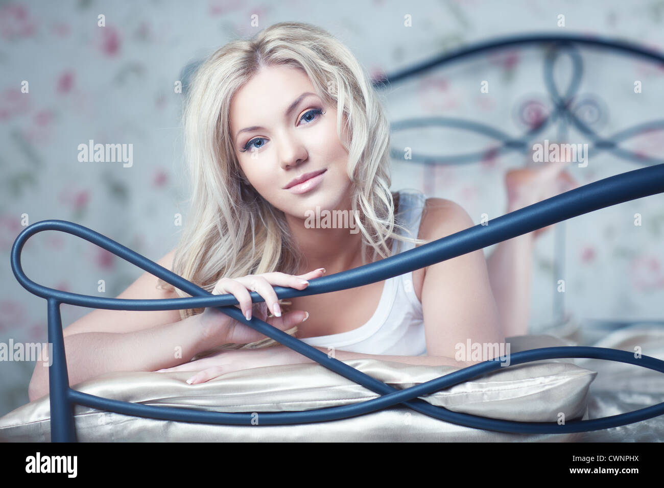 Young woman in bed. Bright white colors. - Stock Image
